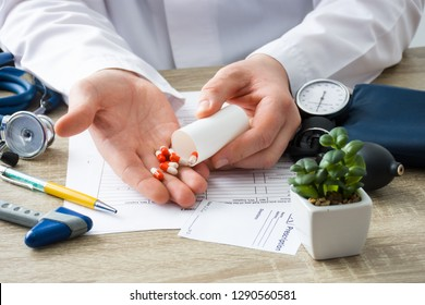 At doctors appointment physician shows patient capsules, which emptied into hand from container with focus on hand with drugs. Scene of prescription generic or OTC medications by doctor on visit