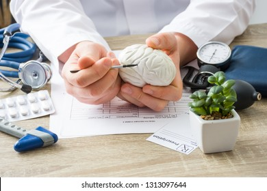 At doctors appointment physician shows to patient shape of brain with focus on hand with organ. Scene explaining patient causes and localization of diseases of brain, nerves and nervous system