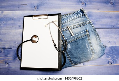 Doctors attributes. Medical insurance. Phonendoscope and paper tablet on jeans background copy space. History of the disease. Medical treatment. Medicine concept. Medical help and consultation.