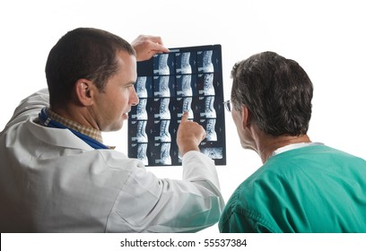 Doctors confer while examining film scans of patient's spine.
