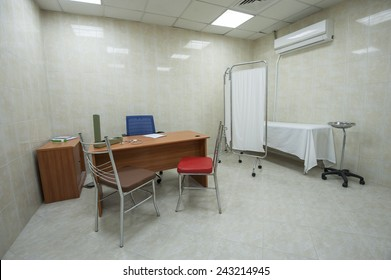 Doctors consultation room with desk and bed in medical center hospital