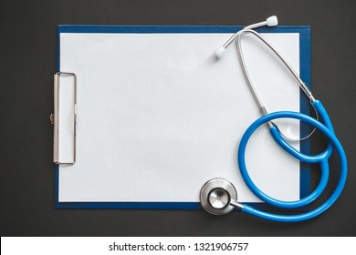Doctor's desk top view, stethoscope and patient's medical record copy space