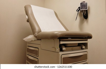 Doctors examination room with exam table and blood pressure instrument on the wall
