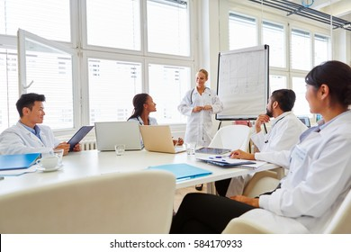 Doctors in flipchart presentation at medical training seminar