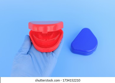 Doctor's hand in a blue glove holds a myofunctional trainer for teeth correction. Blue background. Selective focus.