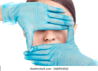 Doctor's hand in gloves around nose of a girl. Woman is preparing to have nose surgery done, isolated cutout on white background. Mixed race latin american hispanic caucasian model