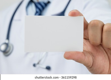 Doctors hand holding a business card