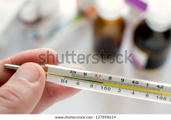 Doctor's hand holding thermometer indicating a high temperature
