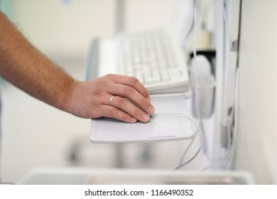 The doctor's hand on a computer mouse near the computer keyboard in the operating room