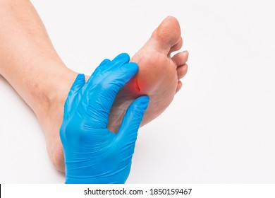 Doctor's hand in a protective medical glove touches and examines the wound on the foot of an elderly woman on a white background