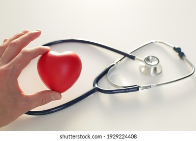 Doctor's hand with stethoscope heart and cardiogram on white background