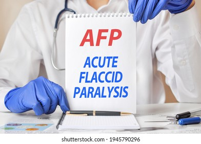 Doctor's hands in blue gloves holding a sheet of paper with text AFP. AFP - short for acute flaccid paralysis, medical concept.