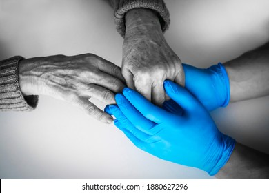 Doctor's hands in a blue gloves holds the hands of an elderly woman, a patient. Handshake, caring, trust and support. Medicine and healthcare.