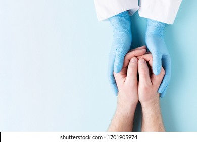 Doctor's hands in gloves holding man's hands. Medical background with copy space. Care concept.