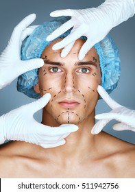 Doctor's hands in gloves touch face of handsome young man. Patient with marker marks on face (forehead, eyes, nose, cheekbone and jaw). Aesthetic Cosmetology concept