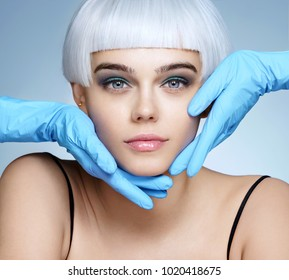 Doctor's hands in gloves touching face of beautiful woman. Photo of fashion blonde model after cosmetic injection. Aesthetic Cosmetology concept