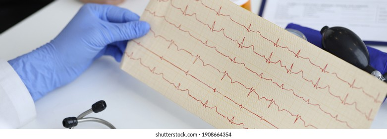 Die Hände des Arztes halten das Ergebnis des Kardiogramms neben dem Sitzen des Patienten. Untersuchung des Konzepts des Herz-Kreislauf-Systems.