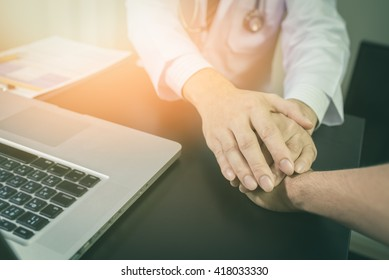 doctor's hands holding  patient's hand for encouragement and empathy.