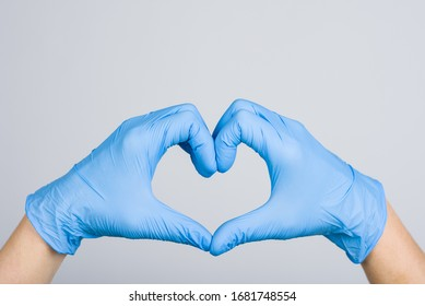 Doctor's hands making heart shape isolated on grey