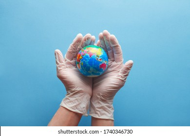 doctor's hands in medical surgical gloves holding earth globe on blue background, world health day and global health care concept