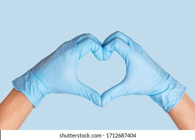 Doctor's hands in protective gloves making heart shape on blue background.