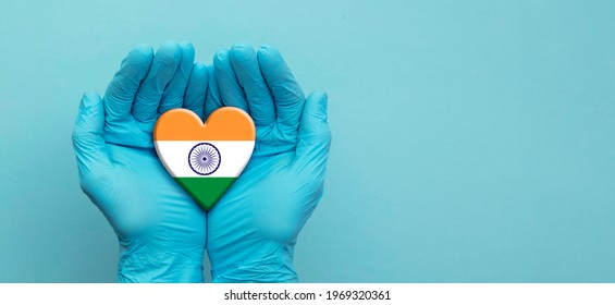 Doctors hands wearing surgical gloves holding India flag heart