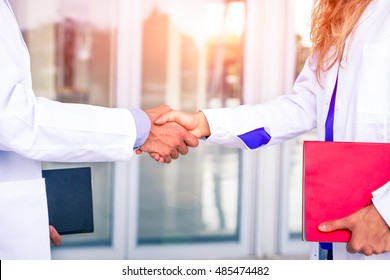 Doctors handshake with white coat holding folders at hospital room entrance - Physician professional business meeting inside clinic hands gesture close up - Concept of team working in medical world
