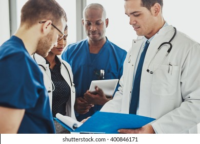 Doctors having a conversation looking at documents, mixed races, surgeons and doctors