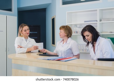 Doctors having discussion hospital reception while people sitting in background