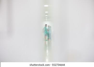 Doctors in hospital. View behind the door blurred.