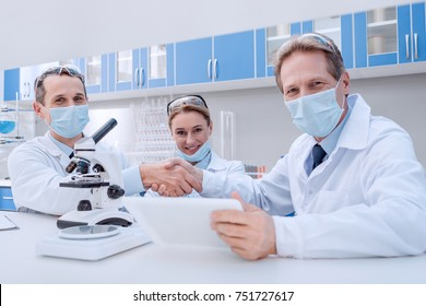 Doctors in lab coats and sterile masks, shaking hands and smiling, while looking at camera