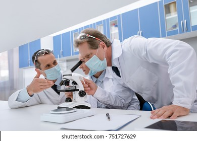 Doctors in lab coats and sterile masks, doing microscope sample analysis and discussing