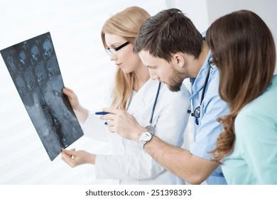 Doctors looking at brain MRI at hospital