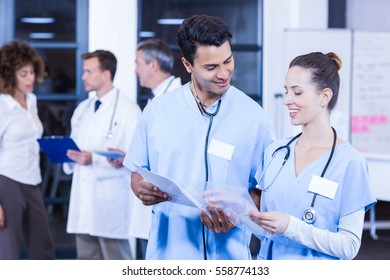Doctors looking at medical report and having a discussion