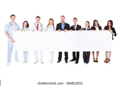 Doctors and managers showing empty banner. Isolated on white