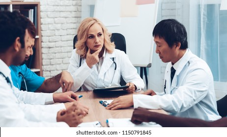 Doctors Meeting. Diagnostic Discussion. Multinational Medicals. Professional Consultation. Patient's Test Results. Young Specialists. Clinician Team Group. Sitting Interns. Surgeon Assistants.