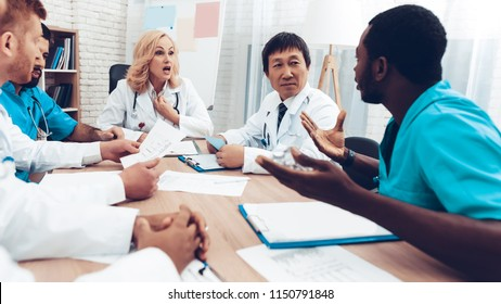Doctors Meeting. Diagnostic Discussion. Multinational Medicals. Professional Consultation. Patient's Test Results. Young Specialists. Clinician Team Group. Physician Assistants. Sitting Interns.