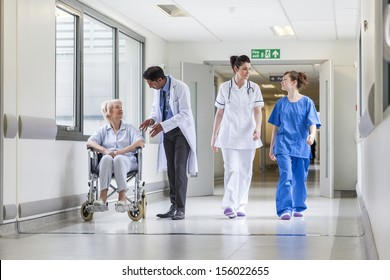 Doctors & nurse in hospital corridor with senior female patient in wheel chair with male Asian doctor