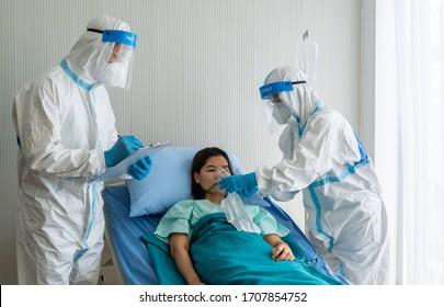 Ärzte in persönlicher Schutzausrüstung oder ppe, die der asiatischen Patientin mit Covid-19 oder einer Coronavirus-Infektion in einer Isoliereinheit im Krankenhaus während einer Pandemie eine Sauerstoffmaske mit Beutel gibt.