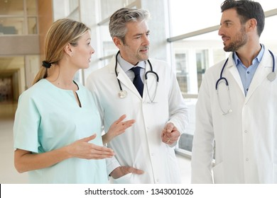 Doctors and nurse talking in hospital corridor