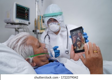 Doctors and nurses are helping elderly corona virus/covid-19 infected patients in the ICU/ hospital, communicating to his family using tablet video call.
