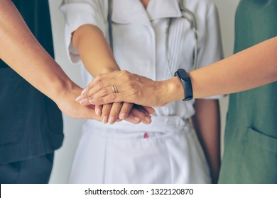 Doctors and nurses in a medical team stacking hands. Surgeon medical people handshaking. Medical personnel in uniform working together in clinic. greeting power of tag team