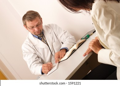 At the doctor's office - doctor is writing out a prescription to his patient