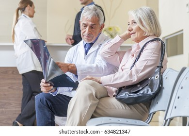 Doctors and patient discussing in hospital waiting room.