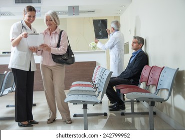 Doctors and patients speaking in the hospital waiting room.