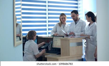 Doctors reviewing patient folders at hospital reception desk