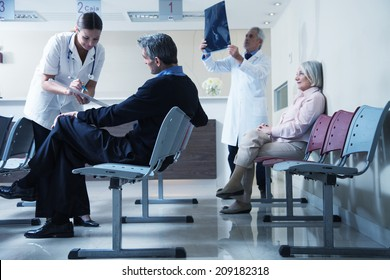 Doctors reviewing x-ray at hospital reception while people sitting in background.
