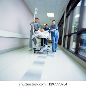Doctors in scrubs rushing patient on hospital gurney through corridor