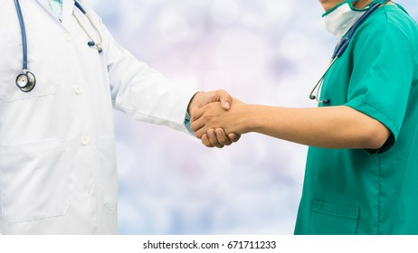 Doctors shaking hands with surgeon, standing on abstract background. Medical people teamwork and collaboration.