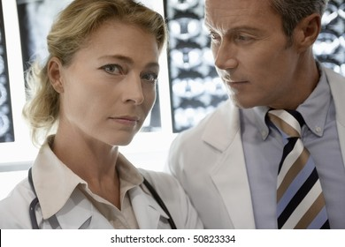 Doctors standing by brain scan images, portrait of woman